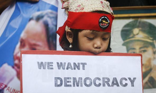 A girl of Myanmar heritage holds a placard during a pro-democracy rally in New Delhi