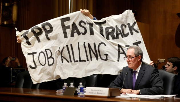 "A man protesting the Trans-Pacific Partnership (TPP) holds a sign over U.S. Trade Representative Michael Froman (R) as he testifies before a Senate Finance Committee hearing on ""President Obama's 2015 Trade Policy Agenda"" on Capitol Hill in Washington January 27,  2015. The top U.S. trade official urged Congress to back the administration's trade agenda on Tuesday and said an ambitious Pacific trade pact is nearing completion.  Froman said the administration looked to lawmakers to pass bipartisan legislation allowing a streamlined approval process for trade deals, such as the 12-nation Trans-Pacific Partnership.  REUTERS/Kevin Lamarque   (UNITED STATES - Tags: POLITICS BUSINESS CIVIL UNREST) - RTR4N6JM"